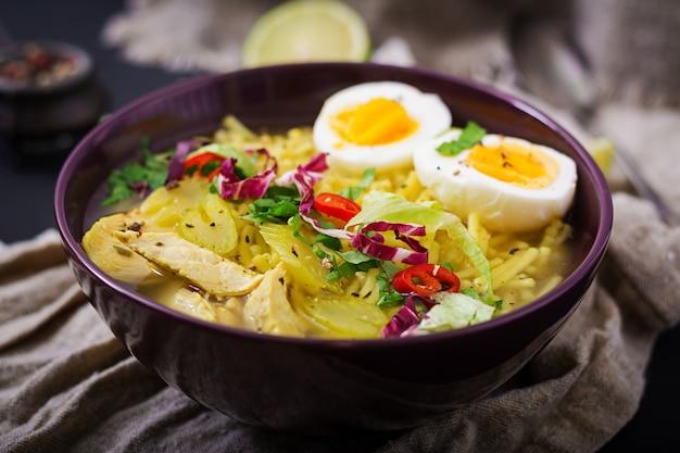 Суп с лапшой с курицей, сельдереем и яйцом в миску на старый деревянный стол.