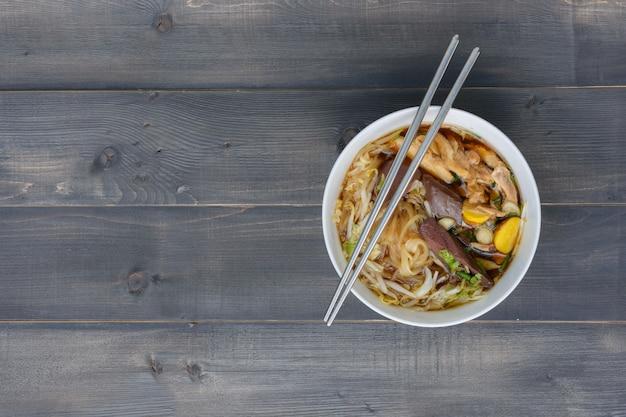나무 탁자 위에 있는 그릇에 젓가락이 든 국수, 최고 전망, 태국 현지 음식