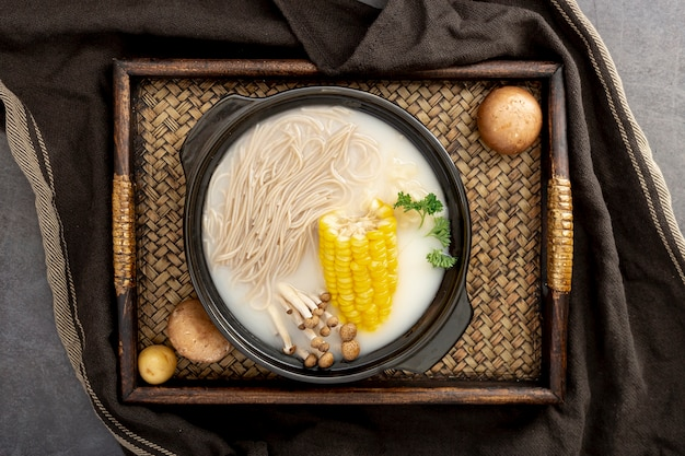 Noodle soup with corn in a black bowl on a wooden table