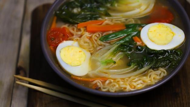 그릇에 계란과 청경채 양배추를 넣은 국수 스프.