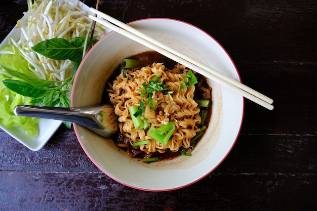 Noodle soup with pork meat and vegetable on wood background