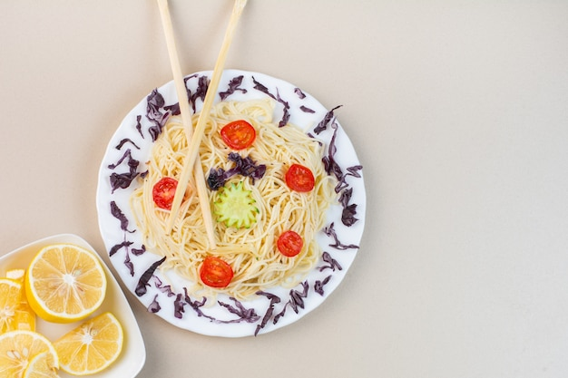 Noodle, tomatoes and chopsticks on a plate next to sliced lemon in a bowl, on the marble surface