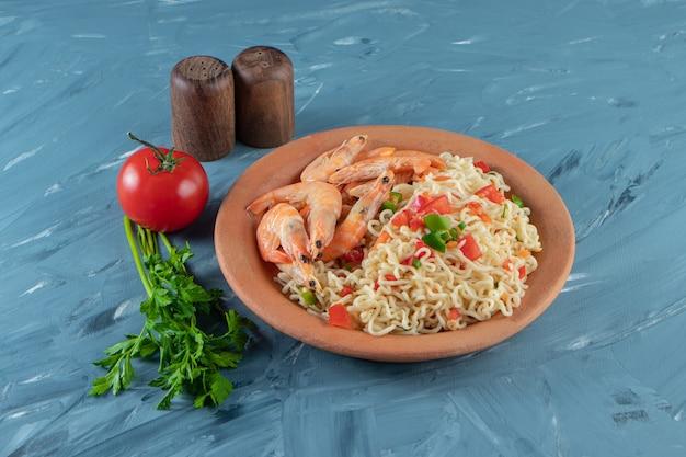 Лапша с мясом на тарелке рядом с петрушкой, помидорами и солью на мраморной поверхности.