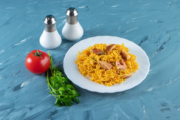 Noodle with meat on a plate next to parsley bunch, tomatoes and salt, on the marble background.