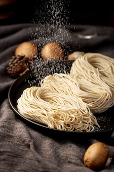 Noodles in a black plate on a grey background with mushrooms