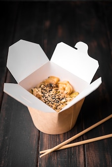 Noodles in box with sesame seeds and chopsticks