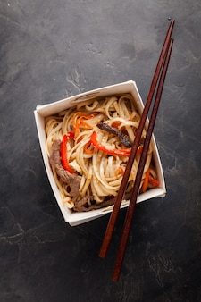 Noodles in a box with vegetables and beef.