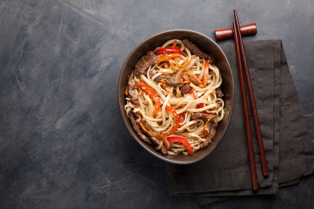Noodles in a glass bowl with vegetables and beef.