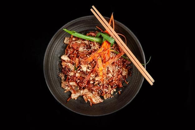 Лапша в черной чаше с кешью, жареный лук, кунжут и морковь с палочками для еды, вид сбоку