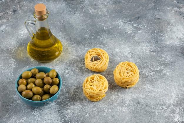 Tagliatelle, olio e olive verdi su pietra.