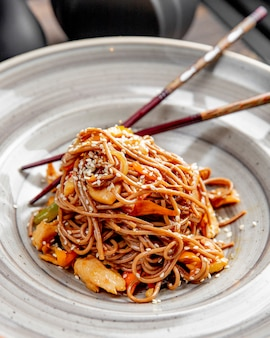 Noodles prepared with chicken peppers sesame seeds and sauce