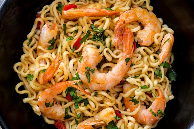 Noodles and shrimps with vegetables in black bowl on wooden table close up
