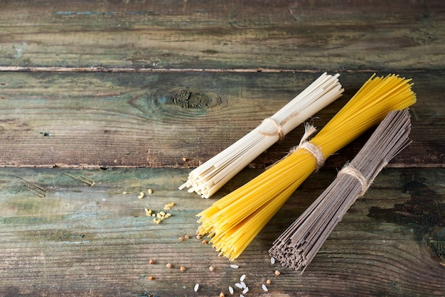 Noodles soba, somen and italian spaghetti on wooden background. traditional japanese food.
