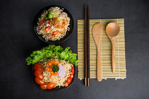 Noodles spicy in the bowl with ingredients and chopsticks, wood spoon on black cement surface