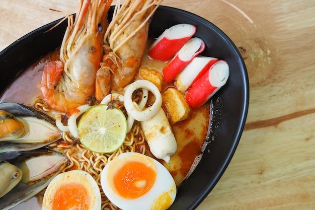 木製のテーブル、トムヤムクンの黒いボウルのスパイシーなエビのスープ