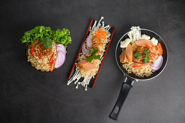 Noodles spicy in wooden tray, frying pans, and bowl with ingredients on black cement surface.