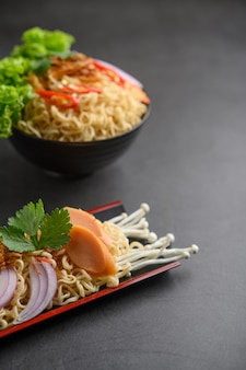 Noodles spicy in wooden tray with ingredients on black cement surface.