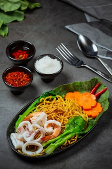 Noodles topped with seafood noodles, crispy noodles, thai food