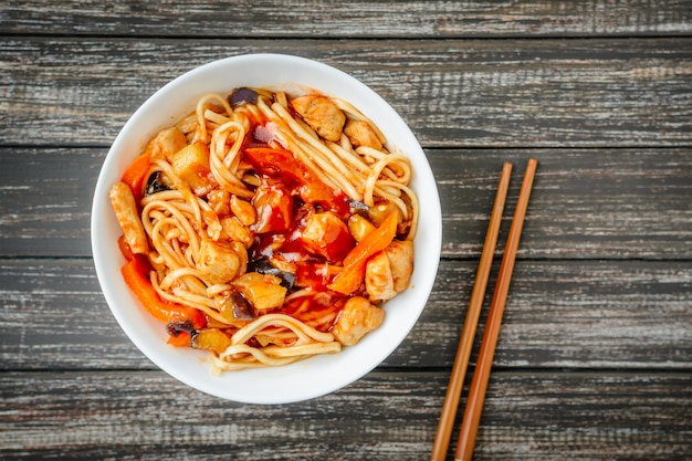 Noodles udon in sweet and sour sauce and chopsticks on wooden table
