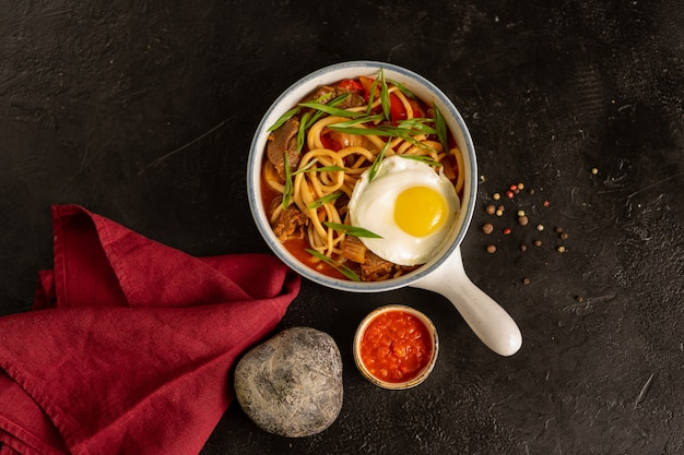 Лапша с говядиной, луком, яйцом, овощами и острым соусом из аджики. тарелка с горячим мясным блюдом на черном столе. вид сверху.