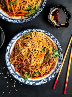 Noodles with beef and vegetables on black table