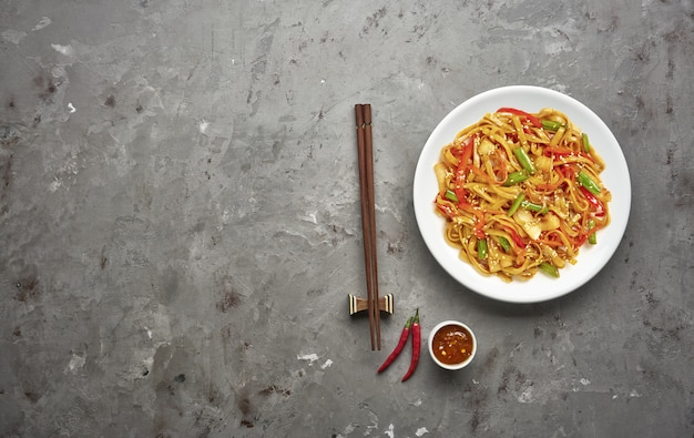 Noodles with beef and vegetables on grey stone table .top view, copy space