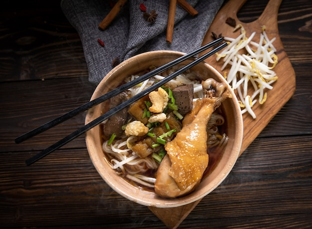 Noodles with chicken leg and chicken fillet, blood with soup thai style and vegetable. boat noodles. selective focus. top view