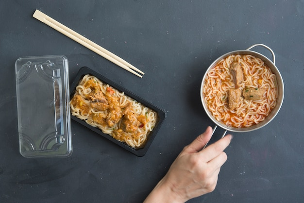 Noodles with chicken meat in bowl on dark table