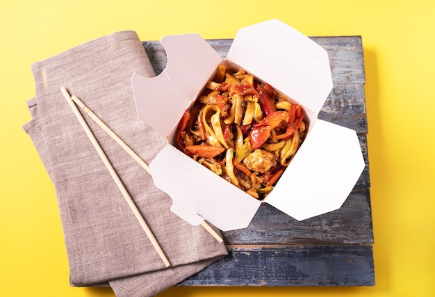 Noodles with chicken and vegetables in a box on yellow