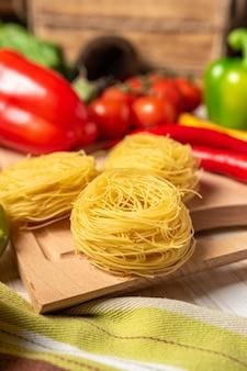 木製のテーブルに色とりどりの野菜とスパイスが入った麺。