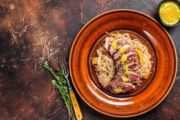 Лапша с стейком из филе утиной грудки на тарелке. темный фон.