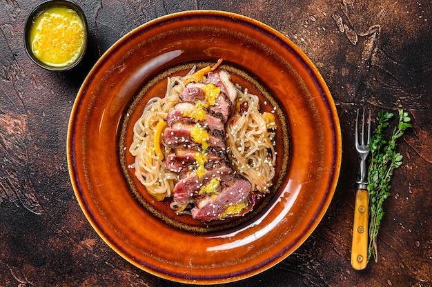 Лапша с стейком из филе утиной грудки на тарелке. темный стол. вид сверху.