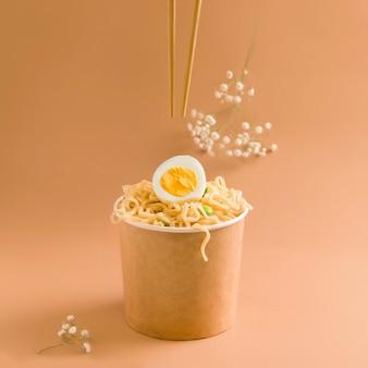 茶色の背景に紙コップに卵と麺。オーガニックスタイル