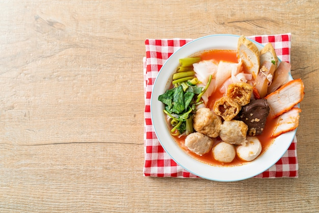 Noodles with meatballs in pink soup or yen ta four noodles in asian style