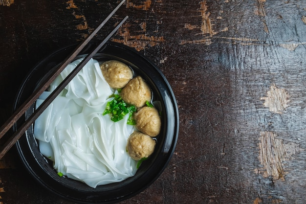 Noodles with meatballs on a wooden table