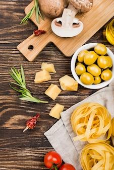 Лапша с оливками и овощами на столе