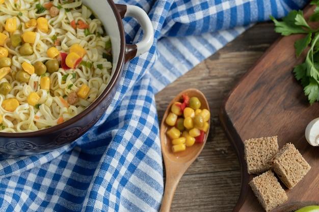 テーブルクロスの鍋にエンドウ豆とトウモロコシの麺
