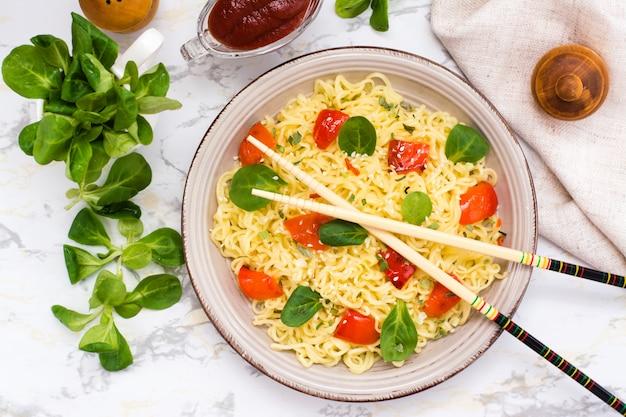 Лапша с перцем, листьями салата и кунжутом в керамической тарелке и палочками для еды. вид сверху