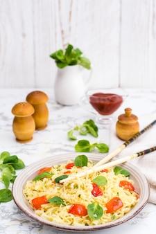 Лапша с перцем, листьями салата и кунжутом в керамической тарелке и палочках