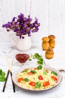 Лапша с перцем, листьями салата и кунжутом в керамической тарелке