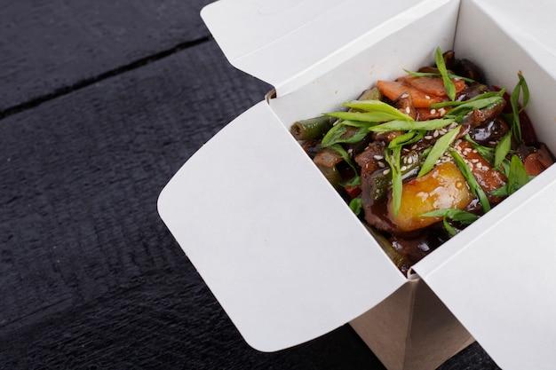 木製のテーブルのテイクアウトボックスで豚肉と野菜の麺