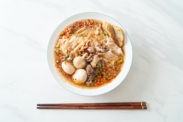 Noodles with pork and meatballs in spicy soup or tom yum noodles in asian style