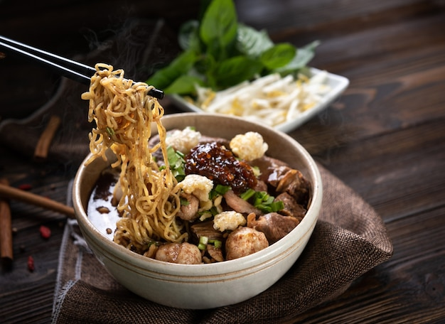 Noodles with pork and pork balls, chilli paste with soup thai style and vegetable. boat noodles. selective focus