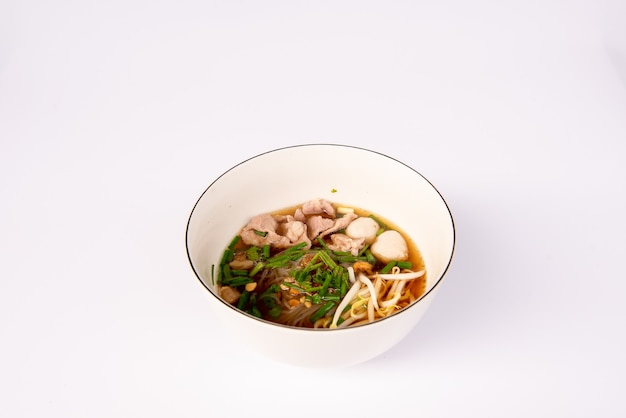 Noodles with pork and pork balls with soup thai style in white bowl