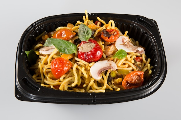 Noodles with pork and vegetables in take-out box to go
