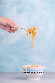Лапша с соусом в цветной миске, рука держит вилку макаронных изделий, спагетти аппетит на синем.