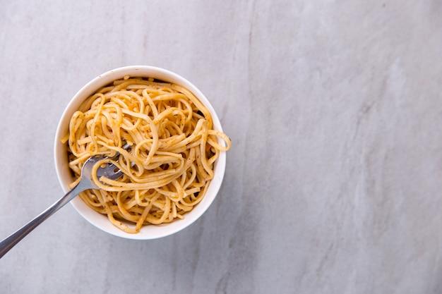 Лапша с соусом в цветной миске с вилкой, аппетитные спагетти на синем.