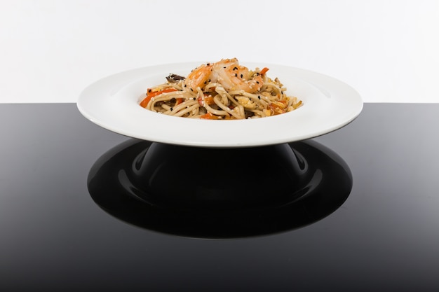 Noodles with seafood on a black table with a white