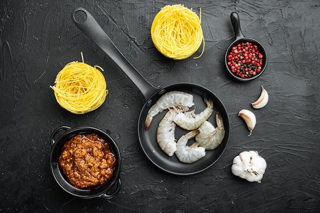 Лапша с набором ингредиентов из морепродуктов, на черном камне, плоская планировка, вид сверху