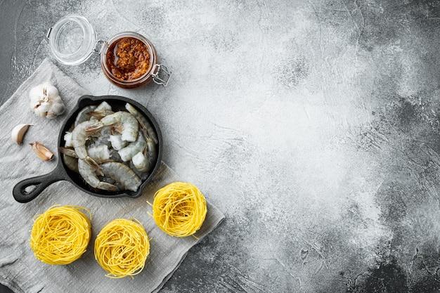 Лапша с набором ингредиентов из морепродуктов, на сером камне, плоская планировка, вид сверху